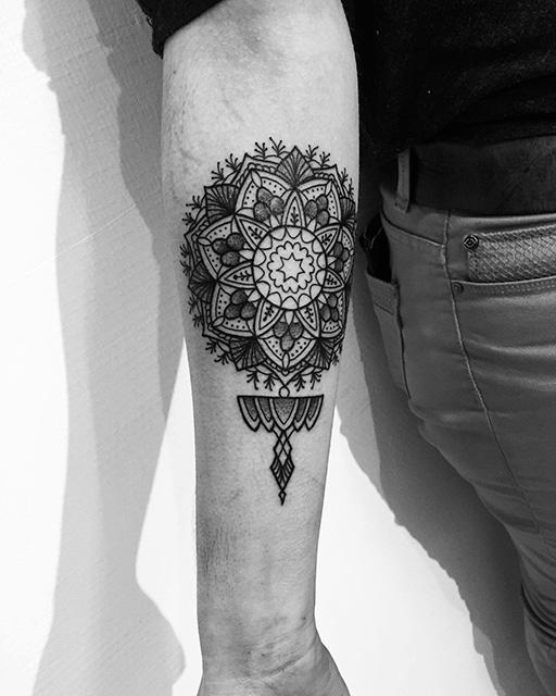 tatouage noir et gris mandala etmédaillon sur avant bras droit